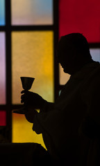 priest lifting chalice  silhouette