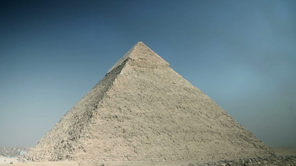 Driving with vehicle by the big pyramid with blue sky