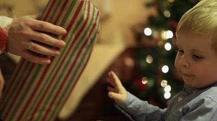 Santa Claus giving a present to a little cute boy