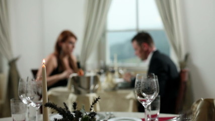 young couple having dinner, while waiter lights the candles for romantic atmosphere