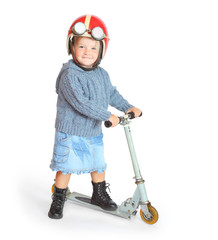 Little girl in retro motorcycle helmet driving her scooter.