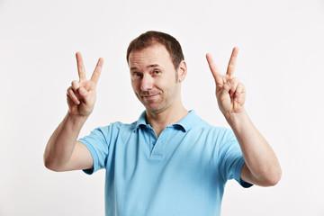 Mann zeigt mit beiden Händen Victoryzeichen