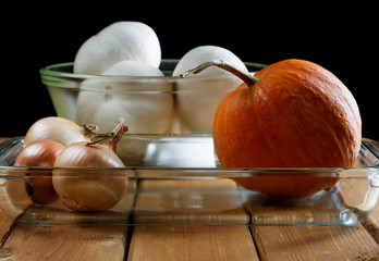 Small pumpkin and onions in a glass plate