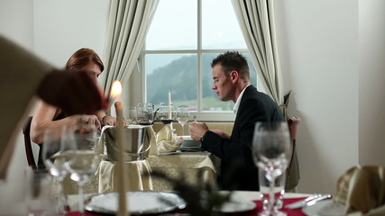 young couple having celebrazing dinner in fancy restaurant while whiter lights the candels for romantic atmosphere