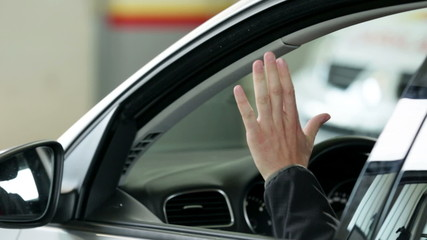 Man entering in car and waving