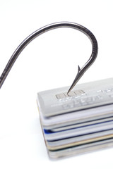 Phishing - A big fish hook on a pile of credit cards