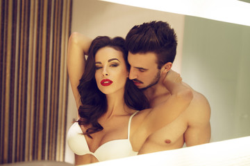 Sexy young couple in mirror at home vintage style