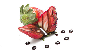 Strawberry with drop of chocolate close up on white