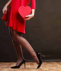Woman in red dress holding heart box.