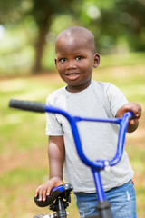 african little boy with his bike outdoors
