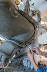 Artist making sculpture statue by wet plaster, lion hand craft