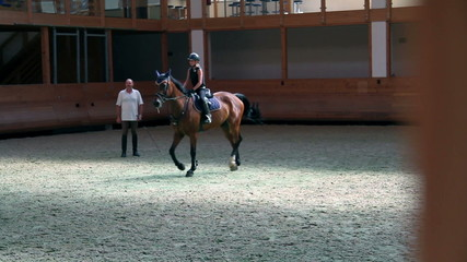 young jockey girl doing circles in training room for equestrianism