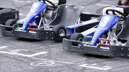 Blue go-carts parked at the starting line on a racing track