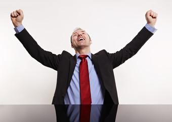 Mann hinter dem Schreibtisch hebt Fäuste in der Luft