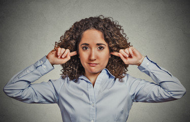 unhappy woman covering closed ears ignoring you