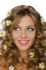 young woman with daisies in curly hair looks away