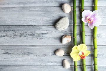 Orchid flowers  and bamboo with pile stones on wooden