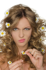 unhappy woman with daisies in hair takes petals