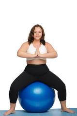 woman with overweight is sitting on blue ball