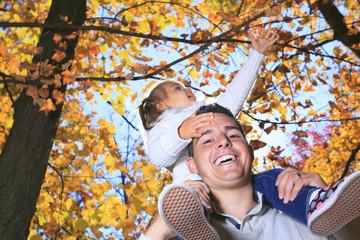 A Family enjoying golden leaves in autumn park