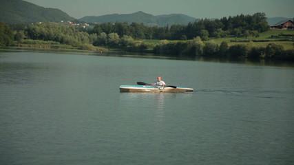 Bald man in big blue kayak on lake