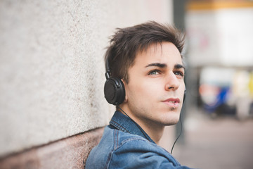 young handsome alternative dark model man in town listening to m