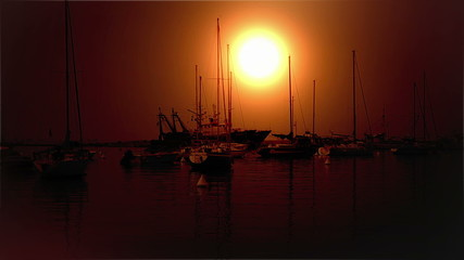 Sunset at seaside with moored boats