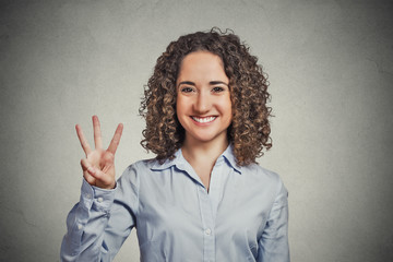 woman showing three fingers sign gesture grey background