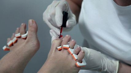 Applying red nail polish on toes in a sterile environment