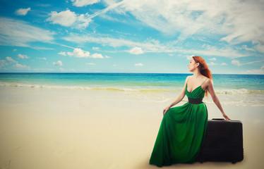 woman sitting on suitcase enjoying ocean view