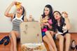 Three beautiful elegant ladies eating pizza while sitting on the