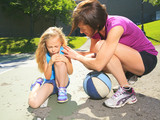A mother play basketball with his daughter how have injury