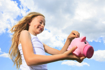 A Piggy Bank and Coin holding by a little girl