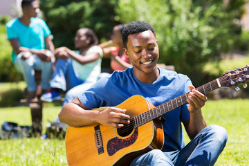 young african american college boy playing guitar