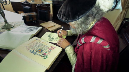 Writer in medieval clothes writing in caligraphy