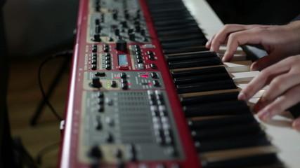 close up shot of musican playing keyboards
