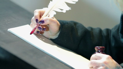 Close up on woman hands writing on paper with real feather pen
