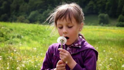 Shot of little girl blowinf dandelion's blossom