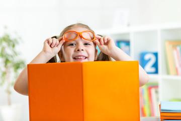 clever child girl behind of open book indoor