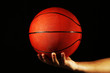 Basketball player holding ball, on dark background