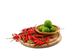 lime and red chillies on wooden chopping board isolated on white