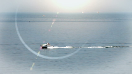 Shot of the speedboat on the sea with a lens flare in the camera