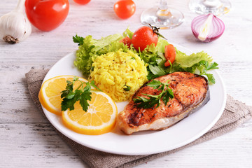 Tasty baked fish with rice on plate on table close-up