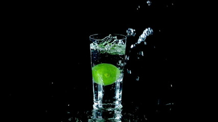 Whole lime falls into glass of water and spurts water around the table