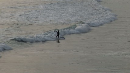 Surfer falls into the sea from a surf. Longest bicycle competition over United States of America - RAAM in 2009.