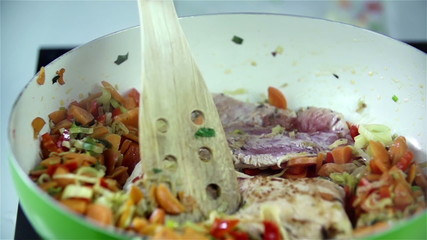 Stiring vegetables and steak with ladle