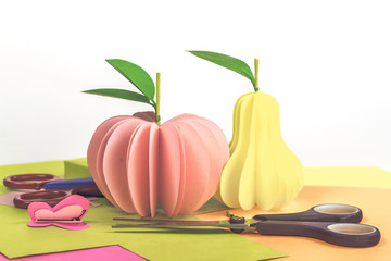 isolated paper fruits - pink apple and pear on color background