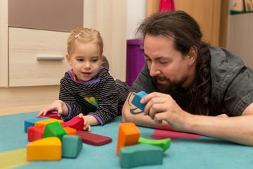 Vater und kleines Kind spielen gemeinsam mit Bauklötzen