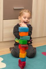 Blondes Mädchen freut sich über Turm aus Bauklötzen