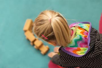 Kleinkind spielt mit einer Eisenbahn aus Holz